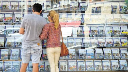 Dos jóvenes miran el escaparate de una inmobiliaria