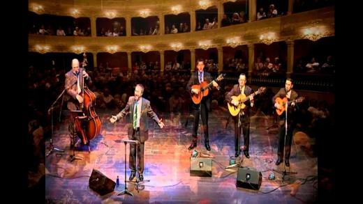 Imagen de Youtube con Lluís Sintes y Arrels de Menorca cantando Escolta es vent en el Principal de Maó.
