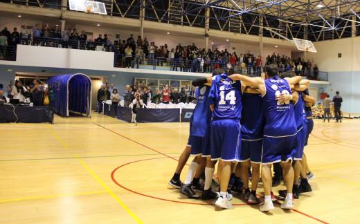 Piña de los jugadores tras un triunfo con el público aplaudiendo de fondo (Fotos: Bàsquet Menorca)