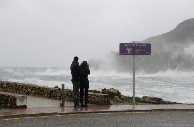 Dos personas, observando el temporal en Fornells (Foto: Tolo Mercadal)