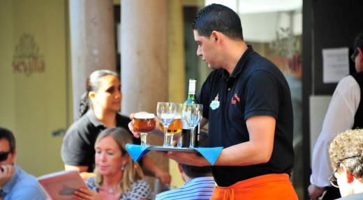 Un camarero atiende a una mesa.