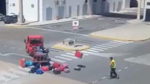 El operario, lanzando las maletas.