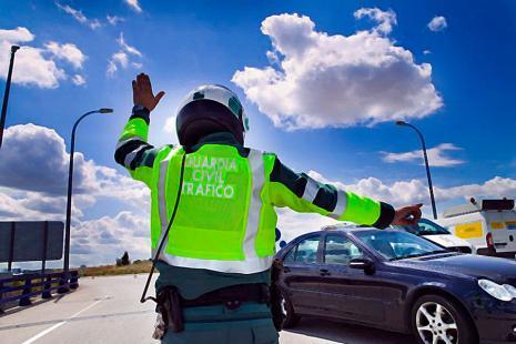 Un Guardia Civil de tráfico detiene a un vehículo.