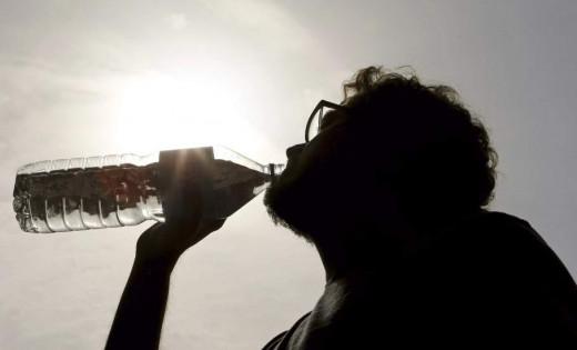 Un hombre hidratándose debido al intenso calor.