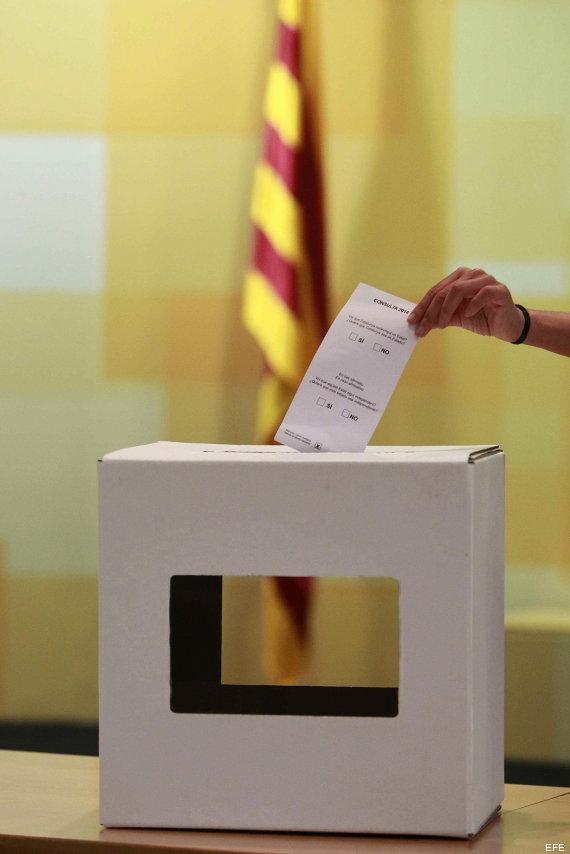 Una persona introduce una papeleta en una urna.
