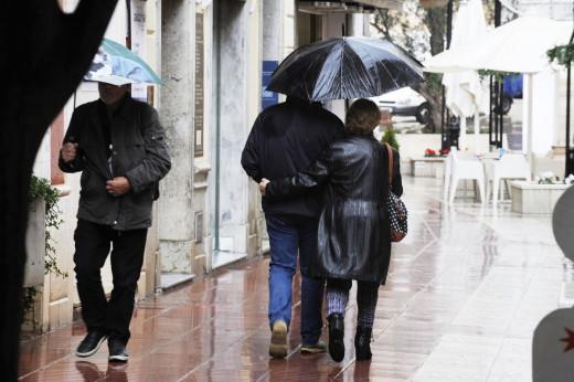 Gente con paraguas en el centro de Maó.