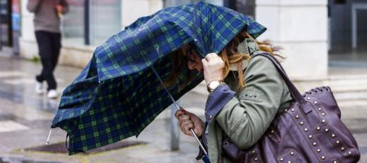 Una mujer se protege con un paraguas.