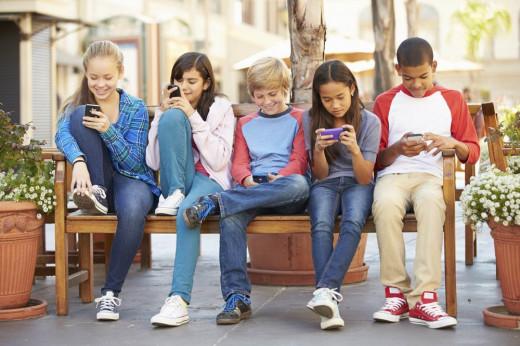 Niños consultando el teléfono móvil.