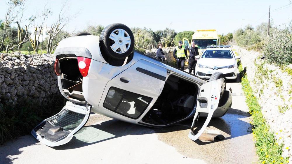 El coche, volcado sobre la vía (Fotos: Tolo Mercadal)