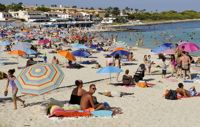 Turistas y residentes en la playa de Punta Prima (Foto: Tolo Mercadal)