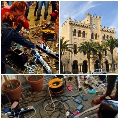 Personas de Ciutadella se reúnen en el ayuntamiento para cargar sus móviles