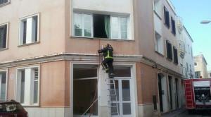 Un bombero, accediendo a la vivienda.