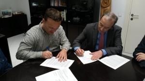 Cristóbal Coll y Ernesto Bonnin firmando el acuerdo.