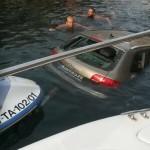 Imagen del automóvil y la moto, semihundidos en el agua.
