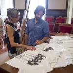 La alcaldesa, Conxa Juanola, admirando las camisetas junto a Fernández, y la ex alcaldesa, al fondo. FOTO.- David Arquimbau