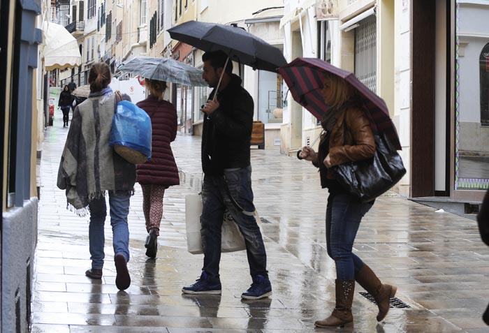 Gente con paraguas en un día de lluvia por el centro de Maó (Foto: Tolo Mercadal)