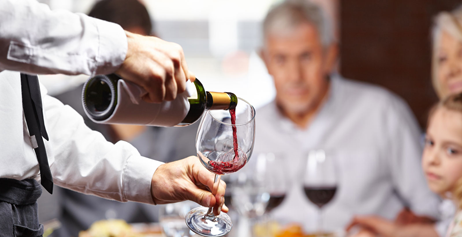 Un camarero sirviendo vino en un restaurante.