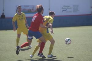 Juanfran protege el balón ante un rival (Fotos: futbolbalear.es)