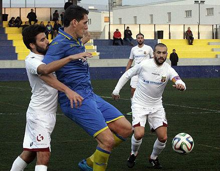 Zurbano trata de controlar un balón ante dos defensas (Foto: Tolo Mercadal)
