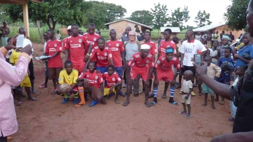 Bonet junto a los jóvenes del equipo de fútbol con camisetas cedidas por el  Liverpool.