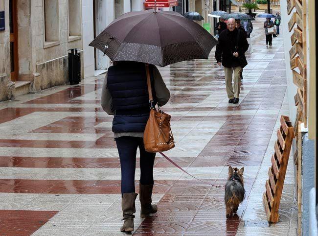 Gente con paraguas en Maó.