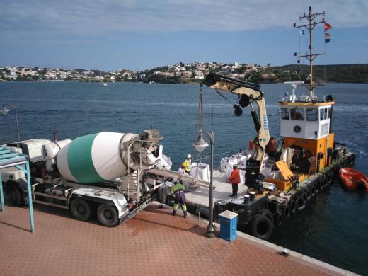 Camión descargando sacas de hormigón en embarcación