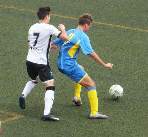 Carlos protege el balón ante un adversario.