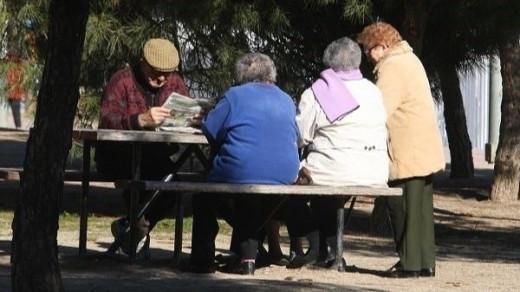 Jubilados sentados en un banco.