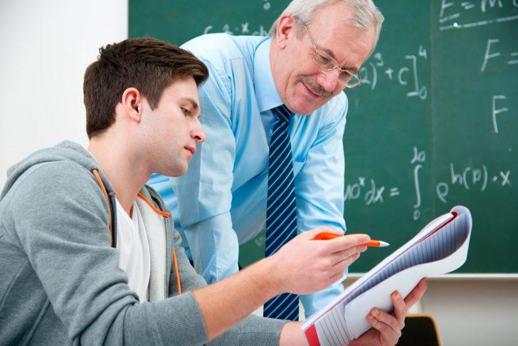 Un profesor atiende a un alumno.