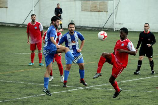 Juan Carlos se lleva el balón ante un jugador del Murense (Foto: deportesmenorca.com)