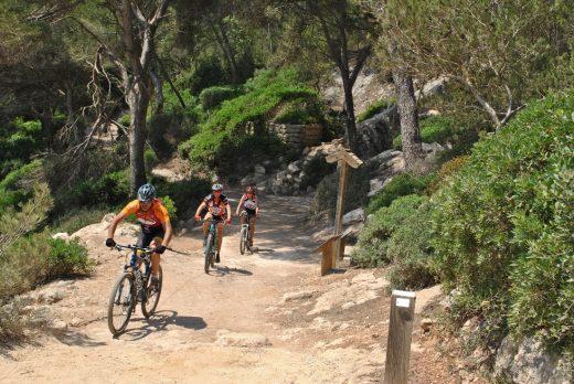 Excursionistas en bicicleta llegando a Cala Mitjana