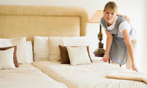 Una empleada hace la cama en un hotel.