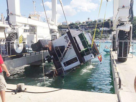 (Fotos) Una casa flotante se hunde en el puerto de Maó y la familia logra salvarse