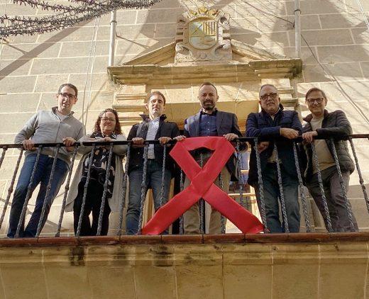 Miembros del equipo de gobierno, junto al lazo rojo (Foto: Ajuntament d'Alaior)