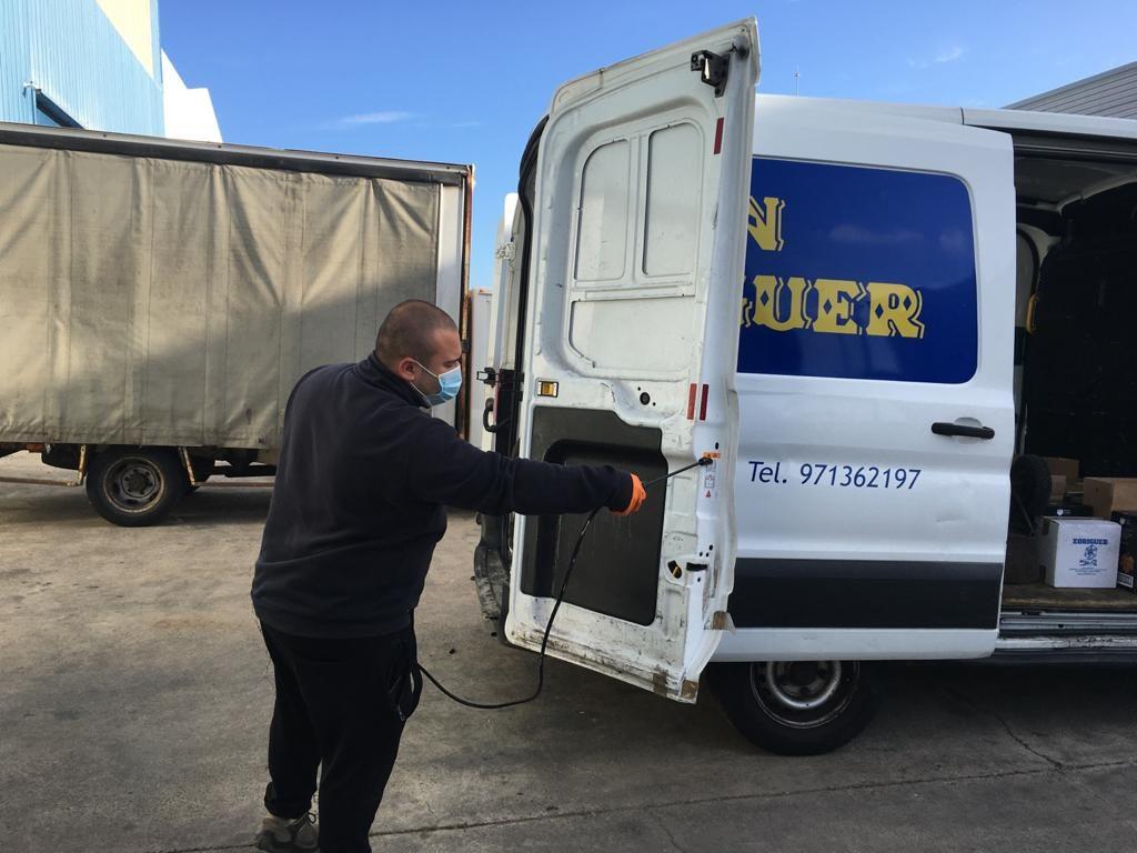 Desinfectando los vehículos para la distribución de los productos Xoriguer