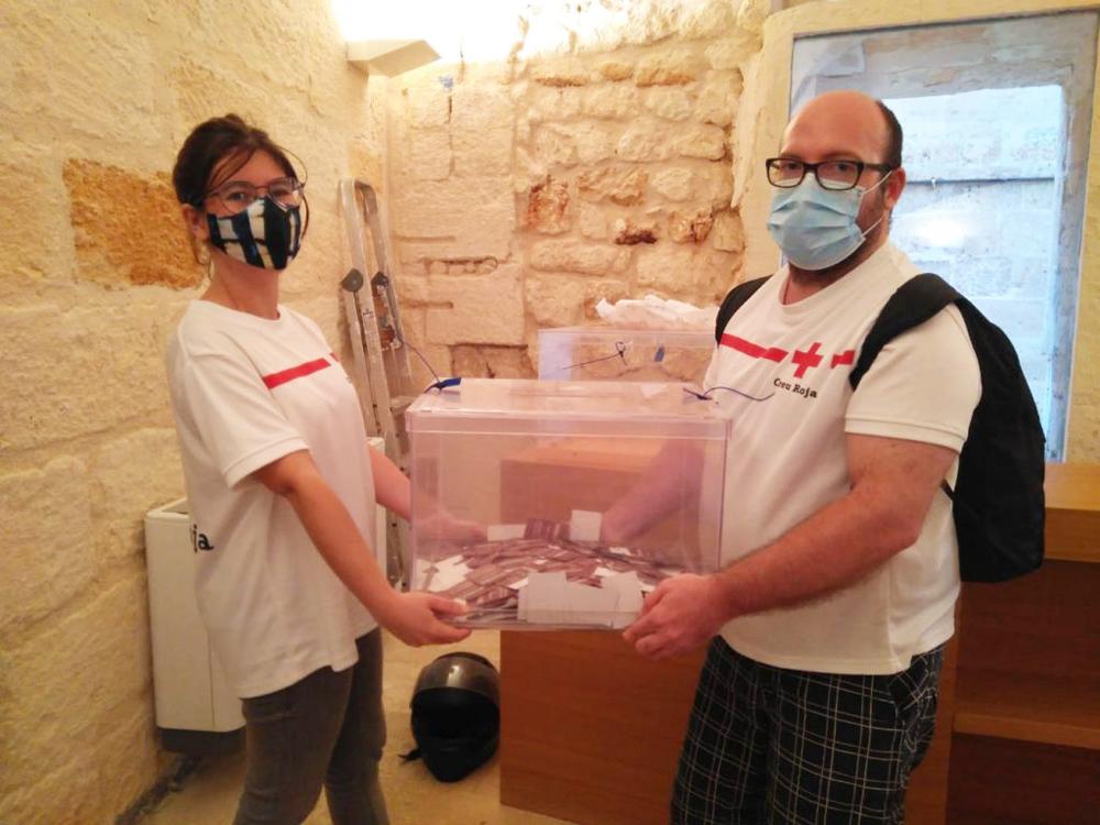 Voluntarios de la Cruz Roja con la urna de las papeletas para la rifa