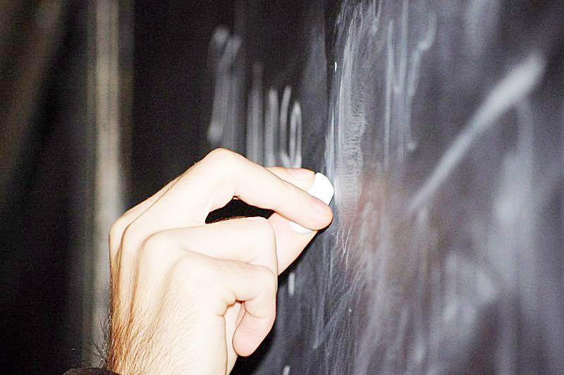 Profesor escribiendo en una pizarra.