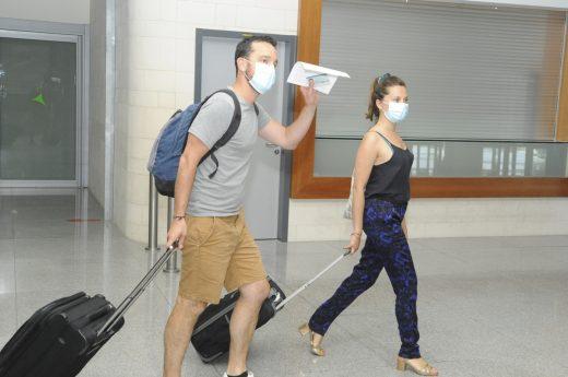 Turistas llegando con mascarilla al aeropuerto.