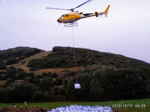 Un helicóptero trabaja en la restauración del empedrado de un tramo del Camí de Cavalls