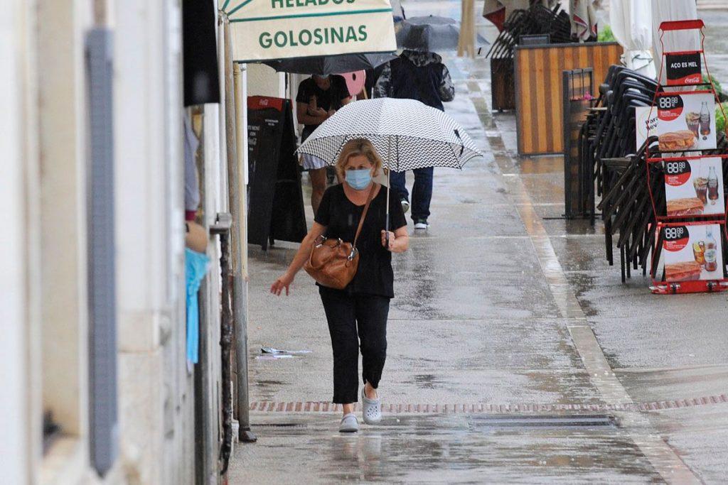 Gente con paraguas caminando por Maó (Foto: Tolo Mercadal)