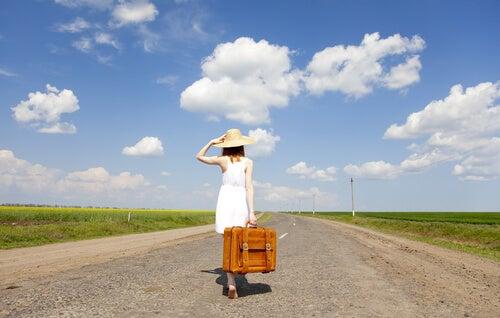 Mujer con una maleta por la carretera.