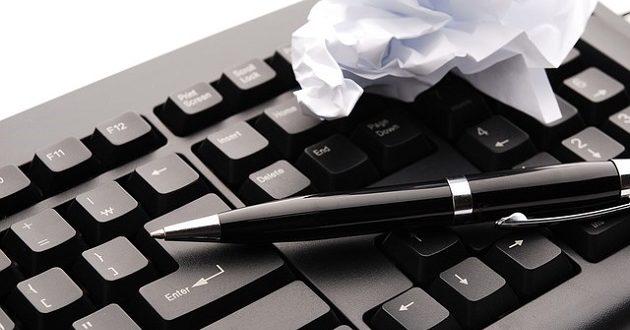 Bolígrafo y papel sobre un teclado.