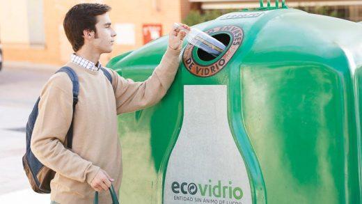 Un ciudadano lanzando un envase de vidrio al contenedor.