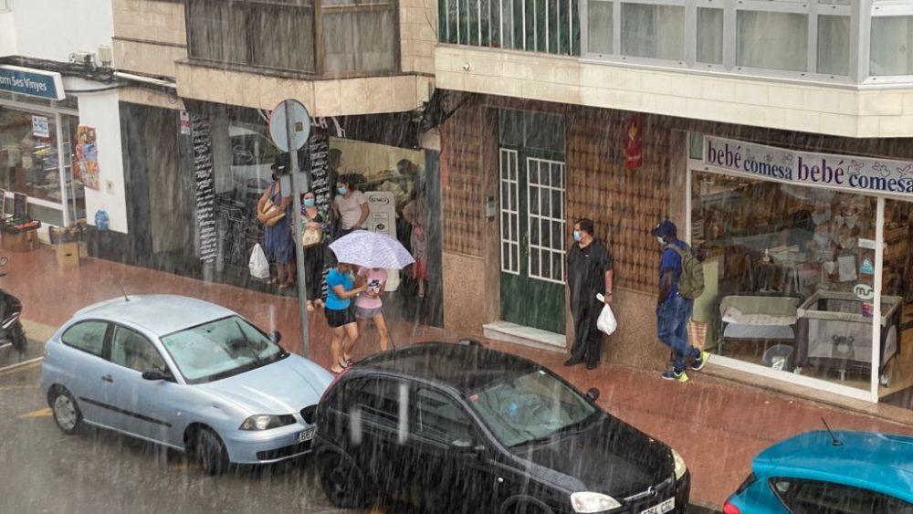 Gente se protege de la lluvia en Maó (Foto: Tolo Mercadal)