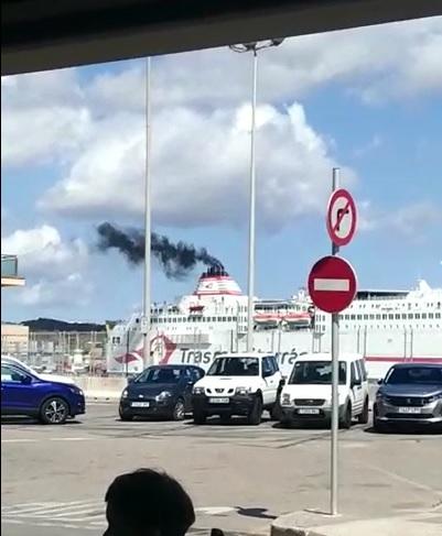 Imagen del humo negro que suelta el barco de pasajeros en el puerto de Maó