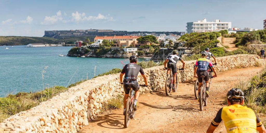 Ciclistas con el puerto de Maó de fondo.